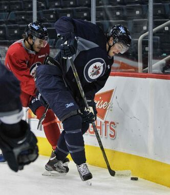 Prized prospect Adam Lowry (right) tries to control the puck while Zach Redmond works him into the corner.