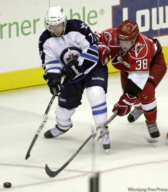 Winnipeg Jets' Kevin Clark (left) and Carolina Hurricanes' Ryan Murphy race for the puck during the third period of their game in Charlotte, N.C., Sunday.