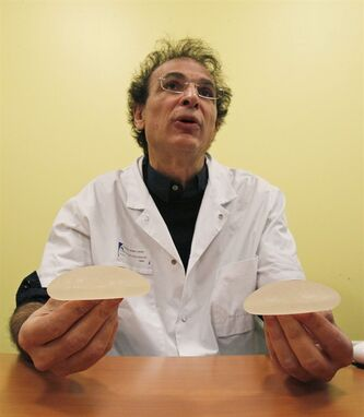 Dr. Maurice Mimoun, a plastic surgeon at the St Louis hospital, holds silicone gel breast implants made by French company Poly Implant Prothese, or PIP, that he removed from a patient because of concerns that they are unsafe, Paris, Wednesday, Dec. 21, 2011. French health authorities are considering whether to suggest that an estimated 30,000 women in France get their breast implants removed, amid warnings by leading doctors about risks of rupture and possible cancer risks. (AP Photo/Michel Euler)