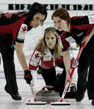 Canada's skip Jennifer Jones, center, watches a stone as her teammates Jill Officer and Dawn Askin, right, sweep during their opening game against China at the World Women's Curling Championships in Gangneung, South Korea. Jones and her team are attempting to win their second straight title.