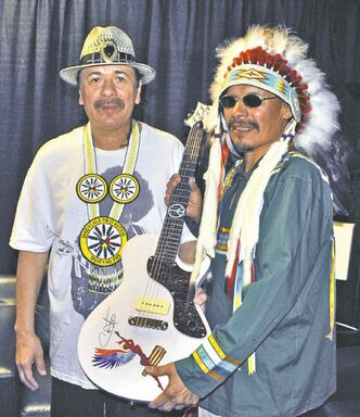 Carlos Santana presents Chief Bart Meekis with a signed guitar backstage before the concert.
