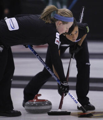 At left, Ashley Howard and Jenna Loder on Team Overton-Clapham sweep a rock in a game against Team Kilgallen at the Scotties Tournament of Hearts in Stonewall, Man., Wednesday.