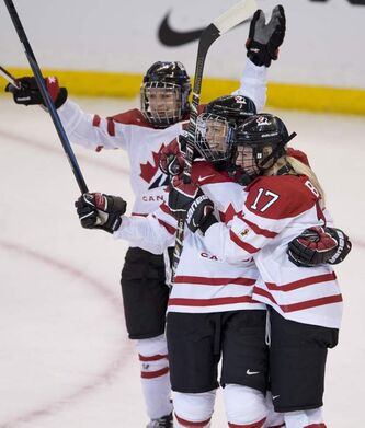 Team Canada players Catherine Ward (top) and Gillian Apps (centre) congratulate Bailey Bram on her goal against Finland at the IIHF Women's World Ice Hockey championships in Ottawa in April. It was her first-ever goal for Team Canada.