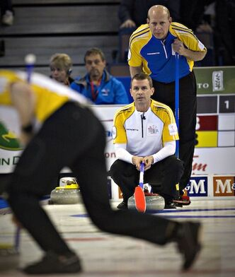 Alberta skip Kevin Martin watches from behind Manitoba skip Jeff Stoughton during their opening-night game at the 2013 Tim Hortons Brier in Edmonton Saturday.