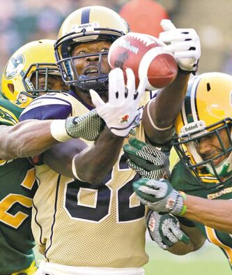 Winnipeg Blue Bomber Terrence Edwards can't hang on as Edmonton Eskimos Marcell Young and Donovan Alexander (right) converge on him during second-half action in Edmonton on Saturday. The Bombers lost again.
