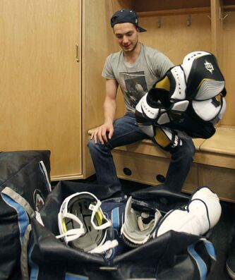 Alex Burmistrov packs up his equipment in the team's dressing room after the Jets played their last game of the 2013 season.