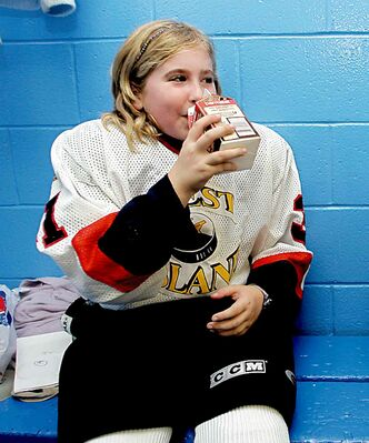 Chelsea Quintal has a drink of chocolate milk after a hockey game.