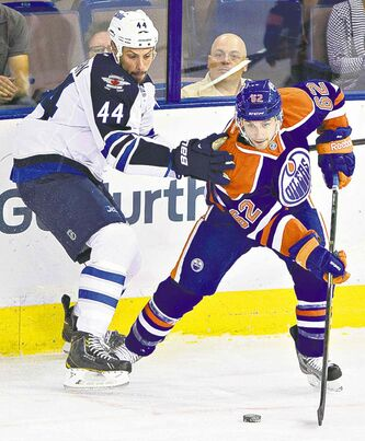Winnipeg Jet Zach Bogosian (left) and Edmonton Oilers� Mark Arcobello battle for the puck in the corner during the first period in Edmonton.