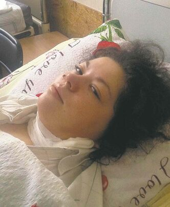 Olesya Zhukovska lies in a hospital bed Friday after surviving a sniper's bullet.
