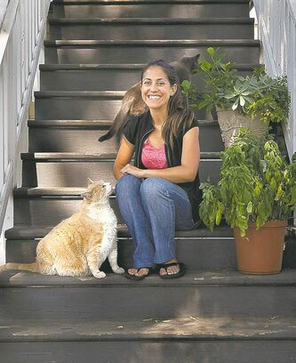 Tyler Lopez sits on her stoop with her cats Norm, left, and Six.
