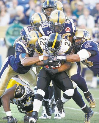 Blast from the past: the Winnipeg defence gang tackles Hamilton running back Avon Cobourne in 2011.
