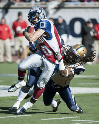 Montreal Alouettes' Bo Bowling (0) is pulled down by Winnipeg Blue Bombers' Alex Suber (21) during first half CFL football action in Montreal, Monday, October 8, 2012.