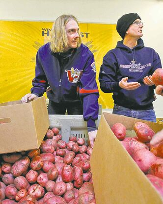 Winnipeg pitcher Brendan Lafferty (left) and GM Andrew Collier pitched in at Winnipeg Harvest Tuesday. Lafferty was the club's bullpen workhorse last season.