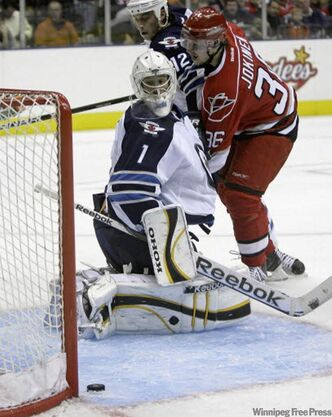 Jets goalie David Aebischer watches a shot by Carolina Hurricanes' Jussi Jokinen slide past the net Sunday.