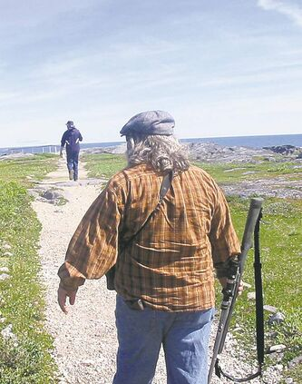 Paul Ratson, tour operator of Nature 1st in Churchill, carries a rifle in case of polar bears while leading a tour group.