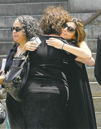 Jamie Lynn Sigler (right), who played Meadow Soprano, is embraced as she leaves the Cathedral Church of Saint John.  the Divine after the funeral service.