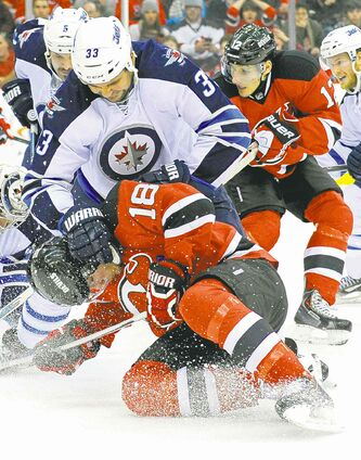 Winnipeg Jets' defenceman Dustin Byfuglien squashes New Jersey Devils' Steve Bernier in the second period.
