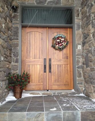 Walnut doors with arched top panels and square lower panels made of verrtical walnut tongue and groove boards. Transom is rectangular glass in walnut frame.