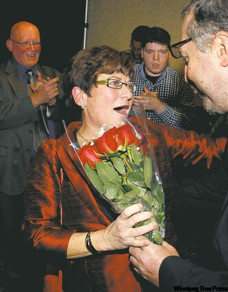 Judy Wasylycia-Leis reacts after getting roses on arrival at rally after polls closed Wednesday.