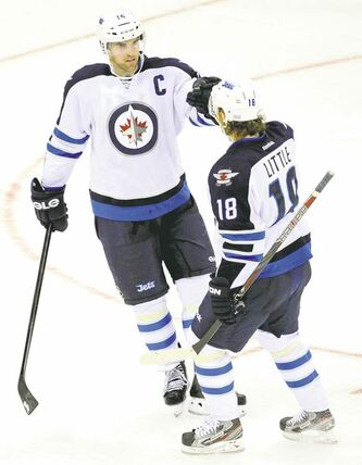 Winnipeg Jets captain Andrew Ladd (left)  celebrates his insurance marker with Bryan Little  during the third period Sunday.