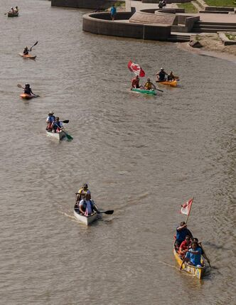 More than two dozen canoeists and kayakers paddle in the Red River from The Forks to Kildonan Park Saturday morning.