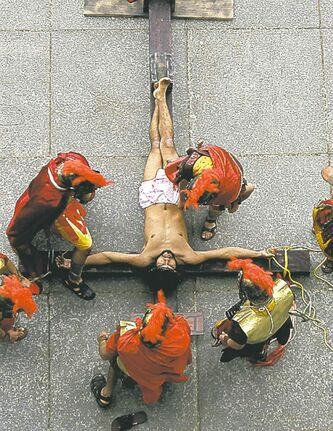 David Amador, 26, playing the role of Jesus, is put on a wooden cross by actors during a passion play performance at Cathedral Basilica of the Sacred Heart in Newark, N.J.