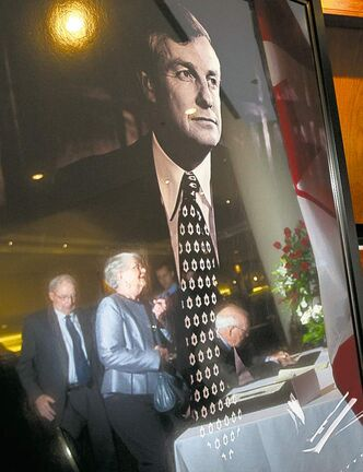 Mourners are reflected in a portrait of Peter Lougheed as they sign a condolence book in Calgary Friday.