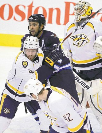 Dustin Byfuglien mixes it up with Nashvillels Kevin Klein in front of Preds goaltender Carter Hutton on Sunday night.