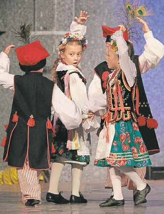 Young dancers perform in front of a castle at the Warsaw-Poland Pavilion.