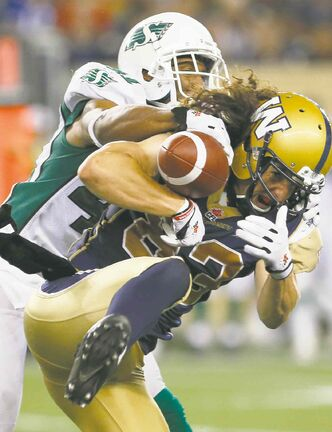 Bombers receiver Julian Feoli-Gudino can't hang onto the ball after absorbing a thundering hit from Saskatchewan Roughrider Tyron Brackenridge.