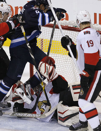 The puck deflects off Winnipeg Jets' Evander Kane (9) to score against  Ottawa Senators' goaltender Craig Anderson as Sens' Colin Greening (14), and Jason Spezza (19) look on during third-period action.