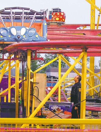 A police officer examines the Crazy Mouse roller-coaster after the accident on Thursday.