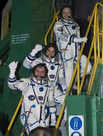 In this image provided by NASA Russian Flight Engineer Alexander Misurkin, top, NASA Flight Engineer Chris Cassidy, and Soyuz Commander Pavel Vinogradov, bottom, wave farewell from the base of the Soyuz rocket at the Baikonur Cosmodrome in Baikonur, Kazakhstan, Friday, March 29, 2013. It was the first time a space crew has taken such a direct route to the orbiting lab. Cassidy, Vinogradov and Misurkin are the first crew to reach the station after only four orbits instead of the standard 50-hour flight to reach the station. (AP PHOTO/NASA, Carla Cioffi)