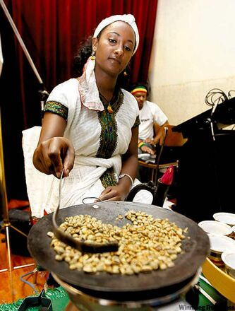 A woman makes coffee at the Ethiopian pavilion.