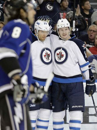 Winnipeg Jets right wing Blake Wheeler (centre) celebrates his first-period goal against the Tampa Bay Lightning with teammate Jacob Trouba (right) during the first period Saturday's game.