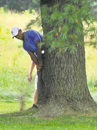 Tiger Woods hits to the fairway from behind a tree on the sixth hole Friday.
