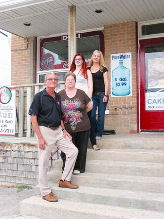 Russ Mierke, owner of Elie Grocery Store, stands with (from bottom) daughter Rena, employee Ashley Fouillard, and daughter Kyra outside the family's store.