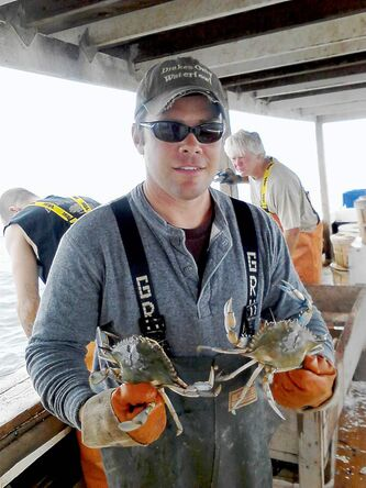 C.J. Canby, 35, holds two blue crabs harvested from Chesapeake Bay aboard his boat Miss Paula.