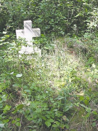 Foliage has overtaken a grave in the old cemetery at the Sadlow Nativity of the Blessed Virgin Mary.