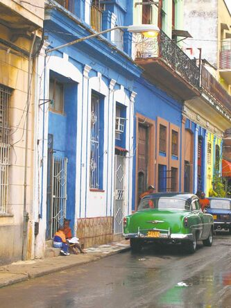 Two Cuban children play on a doorstep in Central Havana. At left, a sign indicates a Casa Particular in Cuba.