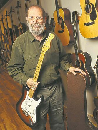 George Gruhn holds the first production model Fender Stratocaster electric guitar.
