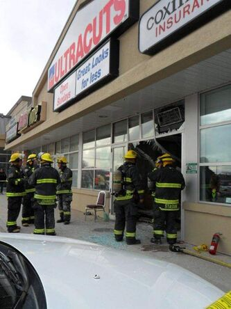 Police investigate the crash at the Ultracuts on Portage Avenue near Cavalier Drive on Saturday, April 7, 2012.