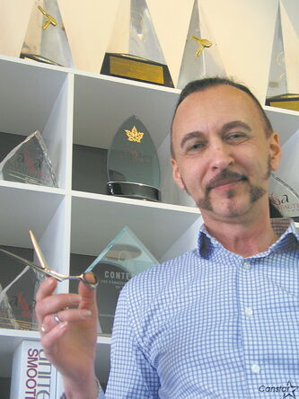 Stylist Ken Hiebert, owner of of Upper Cuts Hair Studio on Corydon, pictured in front of his impressive trophy case.
