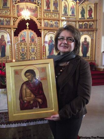 Iconographer Vera Senchuk holds icon.