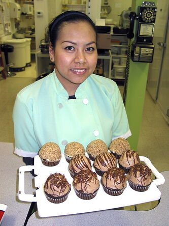 Jane Stangl, co-owner of All About Cakes on St. Mary's Road, holds some of her homemade cupcakes.