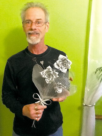 Gary Ganes holding a metal bouquet of flowers he made for his wife when she was ill in 2009, which spawned a new medium for his artistic endeavours.