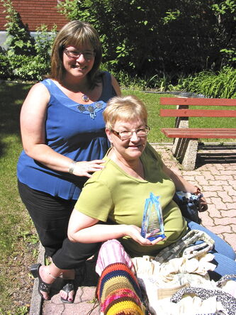 Roslyn Dally (left) and Jo-Anne Pelzer seen with some of the MTS Volunteers' handiwork and Pelzer's recent volunteer award.