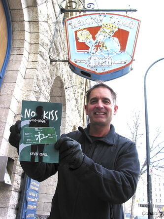 Kevin Zdrill with a copy of his book No Kiss Good-Night outside the King's Head Pub in the Exchange District, which is a featured location in the story.