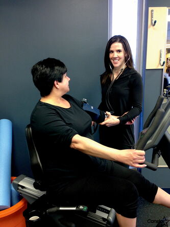 Exercise physiologist Calla Hamilton checks on a client during an exercise session at Creekside Physiotherapy.
