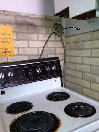 This stove with exposed electrical wiring is in a rooming house in the West End neighbourhood, according to the project website.  Eighteen people share this kitchen, according to the tenant who submitted the photo, who reported paying $355 per month for rent and utilities for their room.